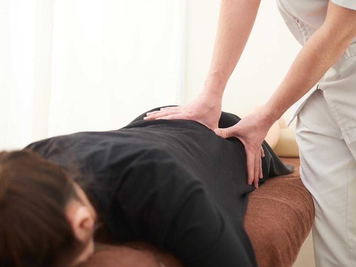 腰の揉みほぐしの施術を受ける女性